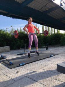 Atletka procvičuje techniku vzpírání v rámci tréninku CrossFit Kids
