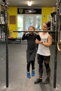 Děti trénují přítahy na hrazdě na lekcích CrossFit Kids