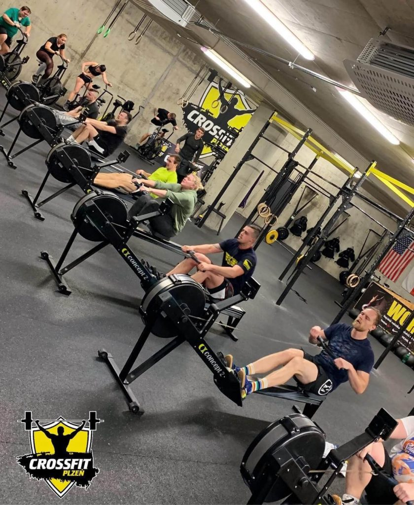 Tréninky CrossFit Pzeň - členové veslují a jedou na Air Bike